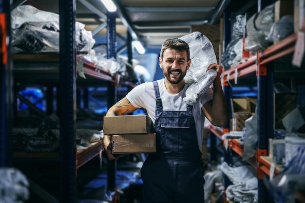 Lächelnder bärtiger tätowierter fleißiger arbeiter in overalls, der kisten und taschen hält und sie verlagert, während er im lager der import- und exportfirma läuft.