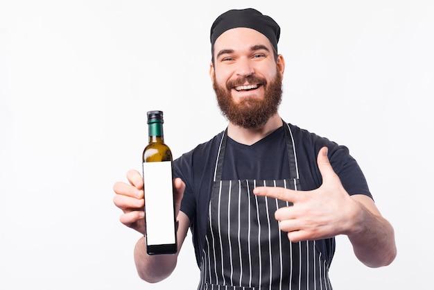 Lächelnder barista mann, der am besten olivenölflasche zeigt