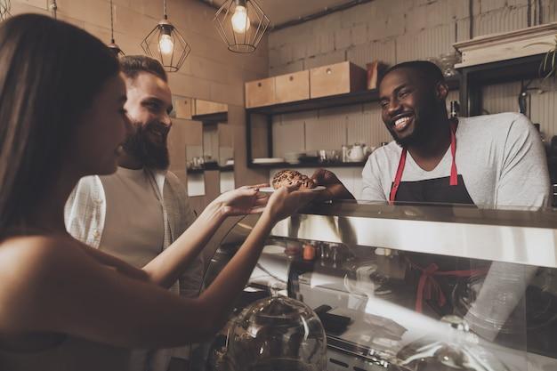 Lächelnder barista mann gibt einem mädchen ihre bestellung