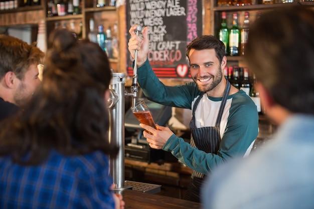 Lächelnder barkeeper, der bier in glas für kunden gießt