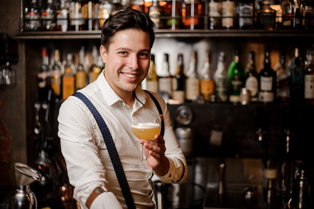 Lächelnder barmann, der ein cocktail am stabstand hält