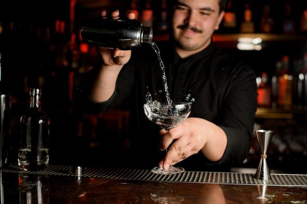 Lächelnder barmixer, der einen transparenten alkohol in das cocktailglas vom stahlrüttler gießt