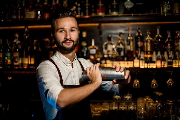 Lächelnder barmixer, der mit einem berufsstahlrüttler macht ein cocktail steht