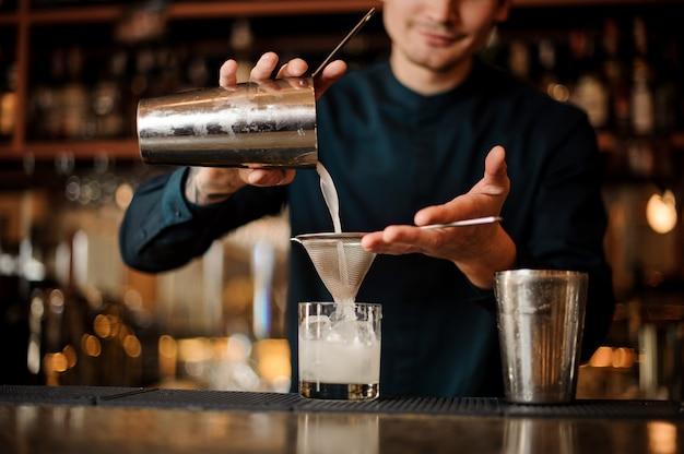 Lächelnder barmixer, der neues getränk von einem schüttel-apparat in ein glas unter verwendung des siebs gießt