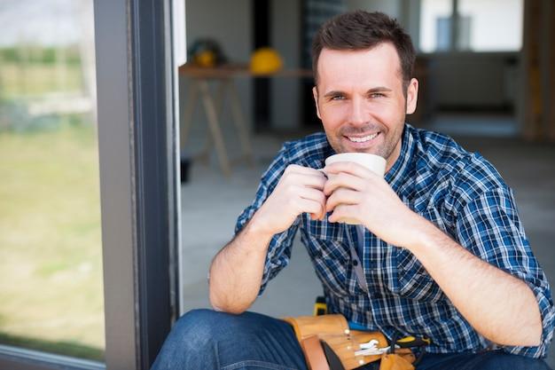 Lächelnder bauarbeiter während der kaffeebremse