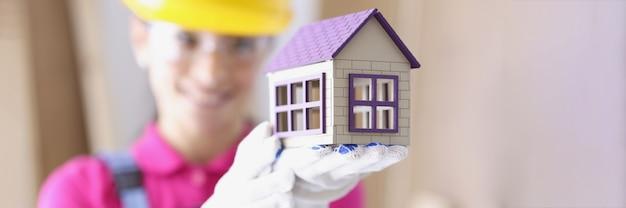Lächelnder baumeister im schutzhelm hält miniaturhaus