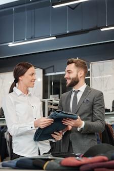 Lächelnder berater im bekleidungsgeschäft, der dem mann jeans gibt, während er ihm bei der auswahl der kleidung im geschäft hilft