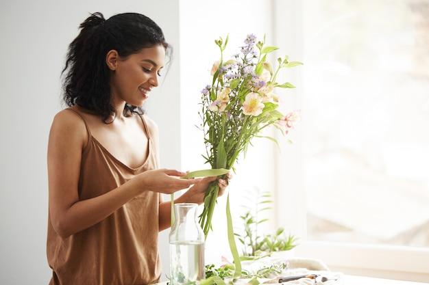 Lächelnder bindender band des schönen afrikanischen floristen, der auf blumenstrauß steht, der nahe fenster am blumenladen steht.