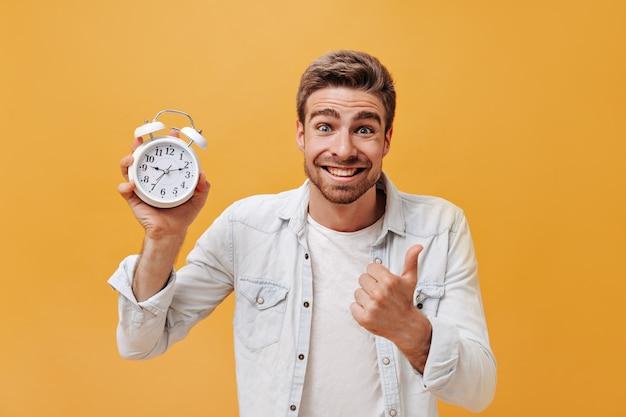 Lächelnder blauäugiger stylischer mann mit dinger-bart in weißem t-shirt und cooler jeansjacke, der in die kamera schaut und mit großem wecker posiert