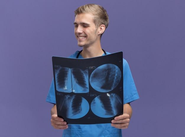 Lächelnder blick auf den jungen männlichen arzt der seite, der arztuniform mit stethoskop hält, das röntgenstrahl auf blaue wand isoliert hält