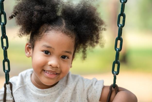 Lächelnder blick des afroamerikanischen kleinen mädchens betrachten kamera am spielplatz im park