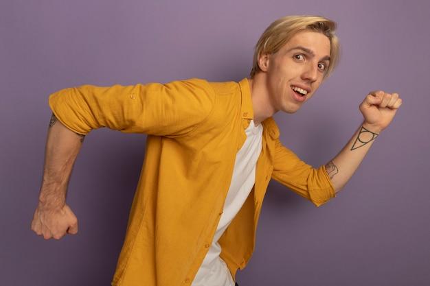 Lächelnder blick geradeaus syoung blonder kerl, der gelbes t-shirt zeigt, das laufende geste lokalisiert auf lila zeigt