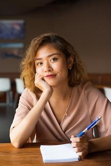 Lächelnder blogger, der artikel am café zeichnet