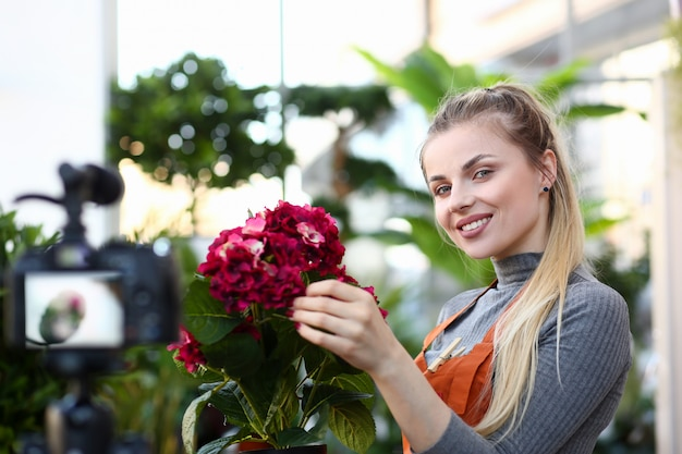 Lächelnder blogger, der rotes hortensienfoto berührt