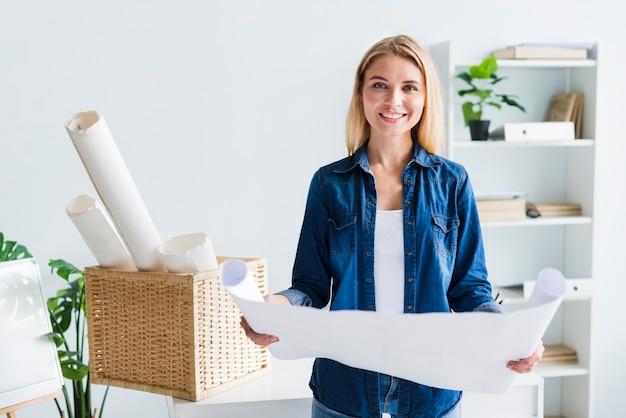 Lächelnder blonder frauendesigner mit großem ausgerolltem papierblatt