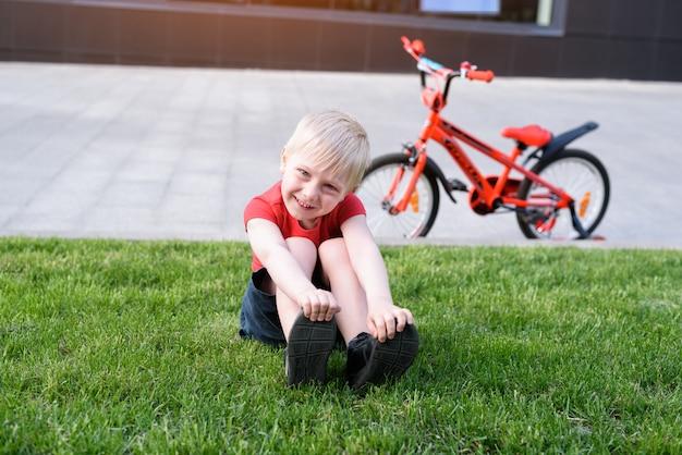 Lächelnder blonder junge, der auf dem rasen stillsteht. fahrrad im hintergrund