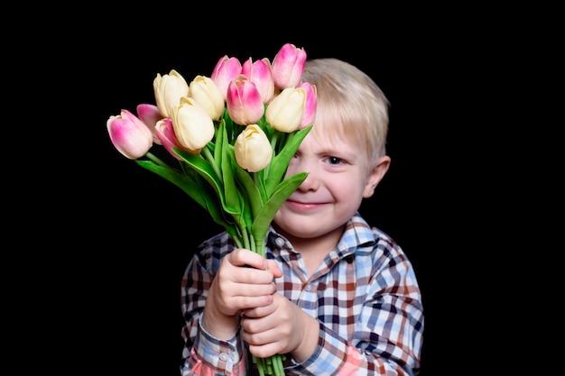 Lächelnder blonder junge des porträts mit einem blumenstrauß von tulpen. schwarzer hintergrund