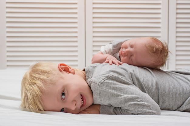 Lächelnder blonder junge und kleine neugeborene schwester, die zurück auf seinem schlafen. familienkonzept