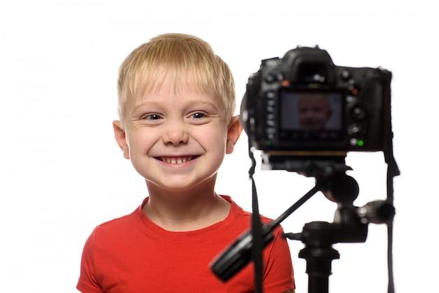 Lächelnder blonder junge vor dem kameraobjektiv. kleiner video-blogger. weiß