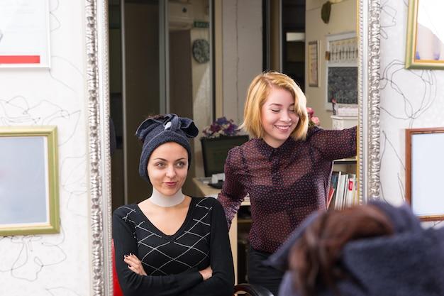 Lächelnder blonder stylist, der neben einer jungen kundin mit nassen haaren steht, die in ein handtuch gewickelt auf einem stuhl mit verschränkten armen im salon sitzen - reflexion im großen spiegel