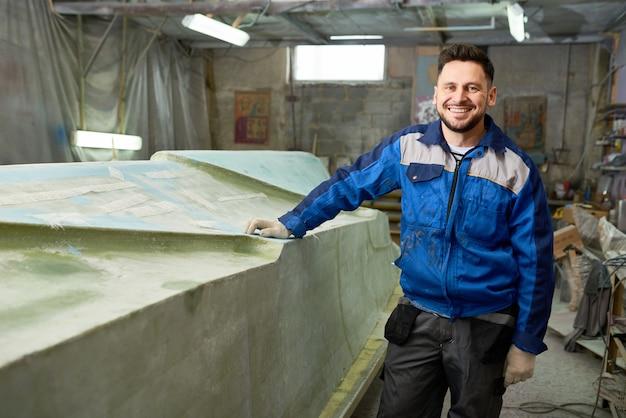 Lächelnder bootsreparaturmann, der in werkstatt aufwirft