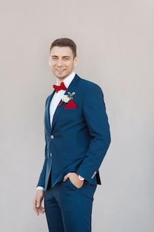Lächelnder bräutigam gegen graue wand