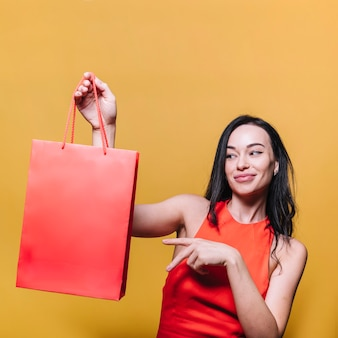 Lächelnder brunette, der einkaufstasche zeigt
