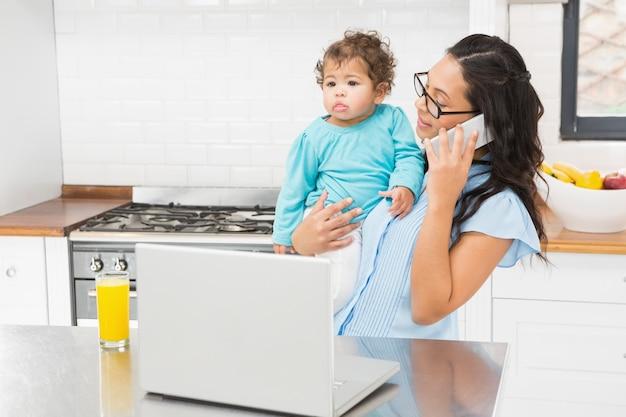 Lächelnder brunette, der ihr baby hält und laptop beim telefonanruf in der küche verwendet