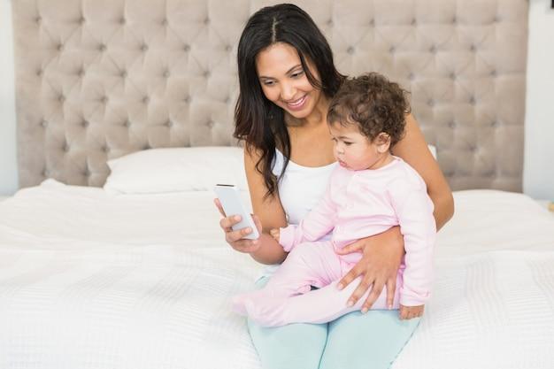 Lächelnder brunette, der ihr baby hält und smartphone auf dem bett verwendet