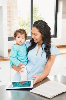Lächelnder brunette, der ihr baby hält und tablette in der küche verwendet