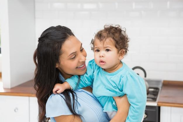 Lächelnder brunette, der ihr baby in der küche hält