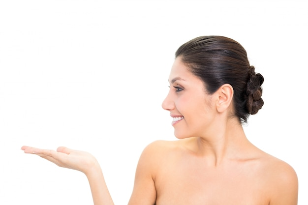 Lächelnder brunette, der mit der hand mit dem kopf gedreht sich darstellt
