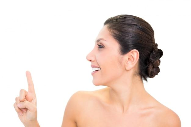 Lächelnder brunette, der oben mit einer hand mit dem kopf gedreht zeigt