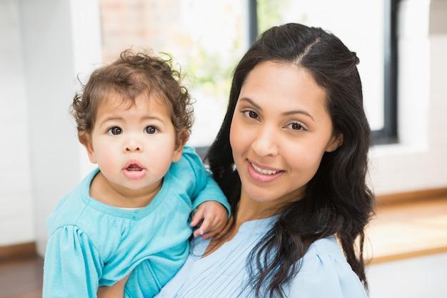 Lächelnder brunette, der zu hause ihr baby hält