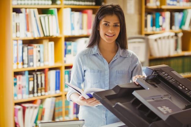 Lächelnder brunettestudent, der eine kopie in der bibliothek macht
