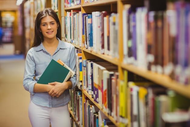 Lächelnder brunettestudent, der nahe bei bücherregalen beim halten von büchern in der bibliothek steht