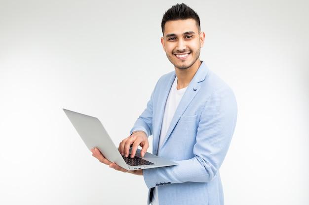 Lächelnder büroangestelltermann mit einem offenen laptop in seinen händen auf einem weißen studiohintergrund