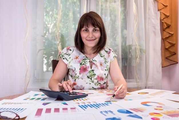 Lächelnder business analyst, der mit grafiken und diagrammen arbeitet