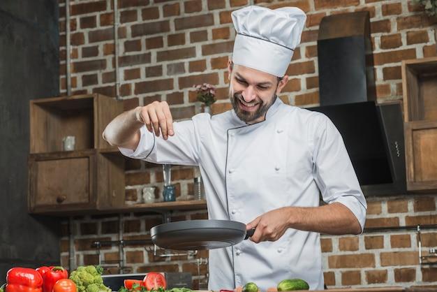 Lächelnder chef, der in der küche spritzt gewürze auf bratpfanne steht