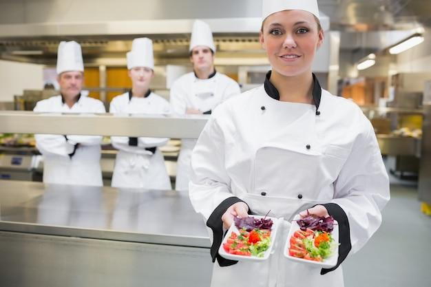 Lächelnder chef, der salate darstellt