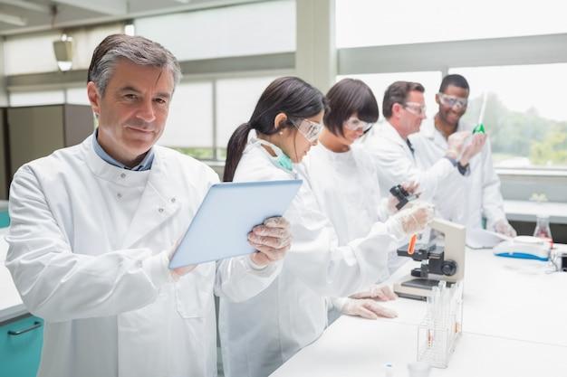 Lächelnder chemiker, der tabletten-pc verwendet