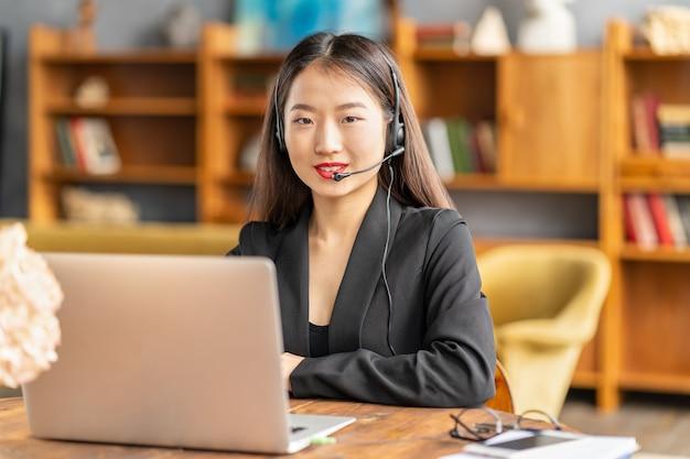 Lächelnder chinesischer support-service-agent, der kunden berät. weibliches porträt, das kamera betrachtet