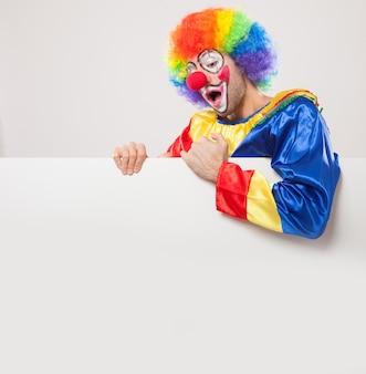 Lächelnder clown, der ein leeres zeichen hält
