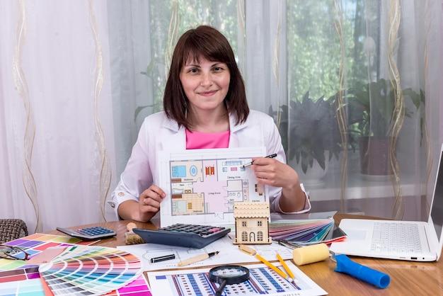 Lächelnder designer, der hausplan im büro zeigt