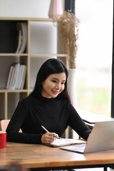 Lächelnder designer der jungen frau, der am kreativen arbeitsplatz sitzt und mit laptop-computer arbeitet.