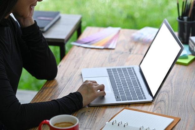 Lächelnder designer der jungen frau, der mit computerlaptop arbeitet.