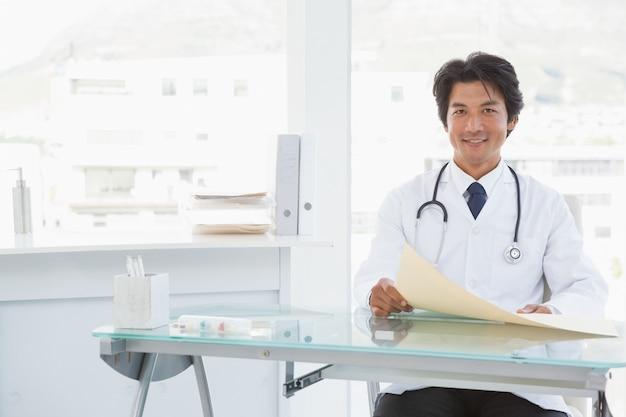 Lächelnder doktor, der an seinem schreibtisch sitzt