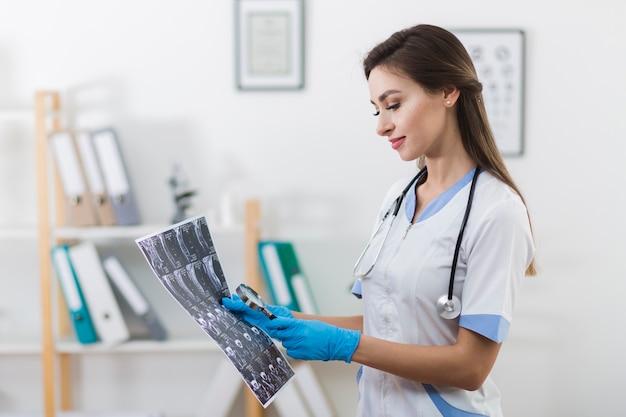 Lächelnder doktor, der eine radiographie betrachtet