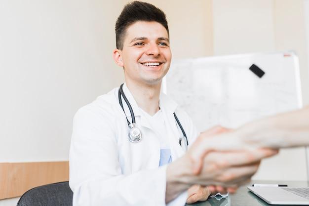 Lächelnder doktor, der hand rüttelt