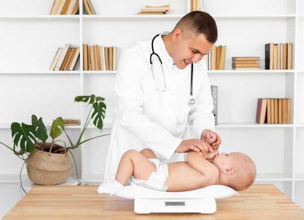Lächelnder doktor, der kleines baby wiegt